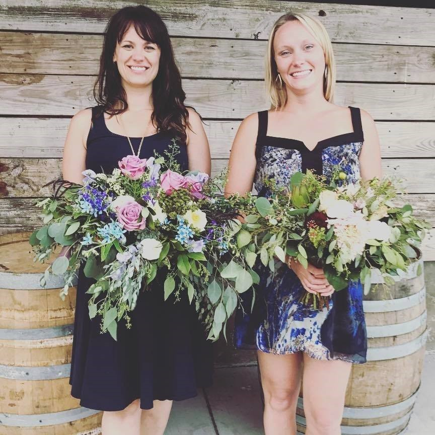 Compass Occasions owners Valerie and Kayla are holding large bouquets of flowers filled will pink roses, white roses, some violet flowers, and a lot of greenery. They are smiling in front of a rustic wooden backdrop and two old whisky barrels.