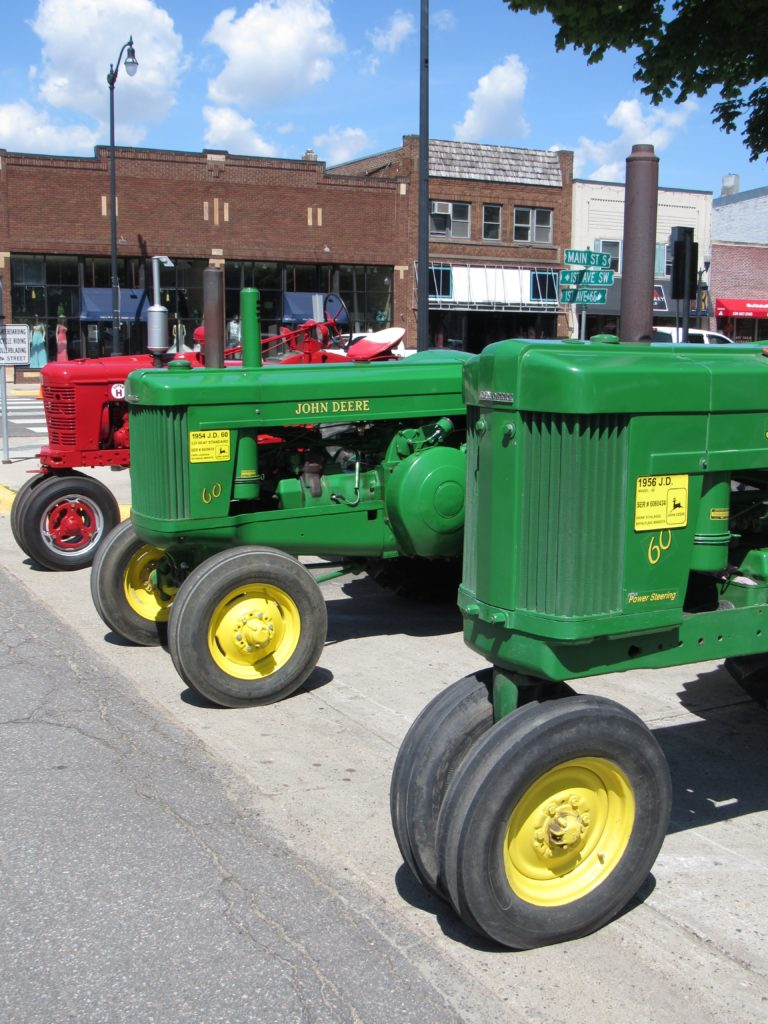 Two green John Deere tractors and one red International tractor at Dairy Days